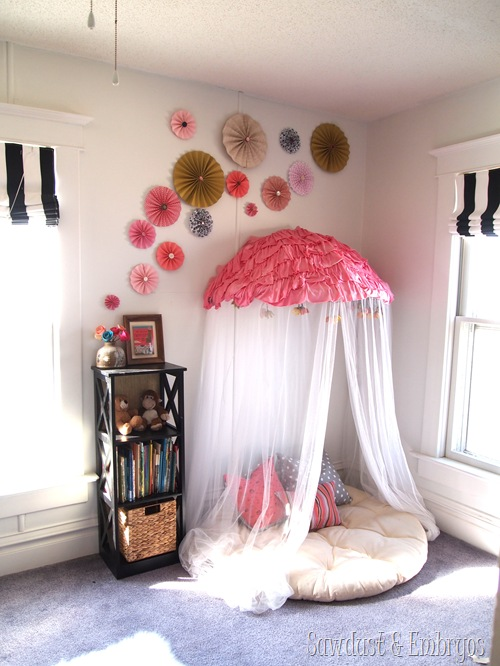 Adding a cute pinwheel collage to a room is an easy decoration addition for a kids room like over this cute reading nook