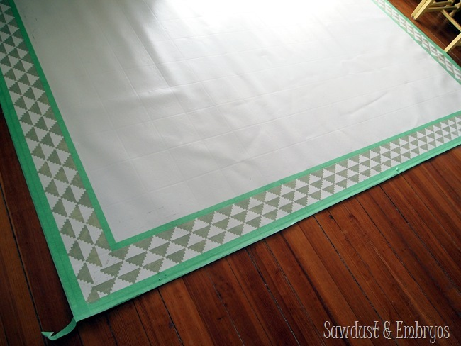 Painting a remnant of linoleum to act as an area rug for the dining room!