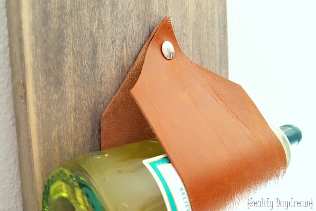 Wall-mounted wine rack... using leather as the slings! {Reality Daydream}