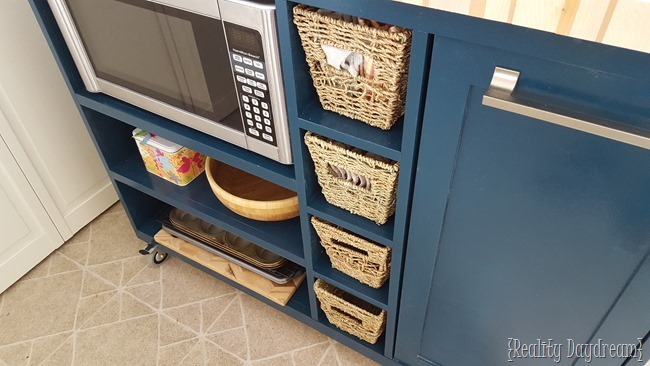 This custom DIY rolling kitchen island was built with a butcher block top, and a place for the microwave and trash!
