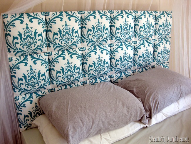 Individual upholstered squares lined up to make a tufted DIY headboard!