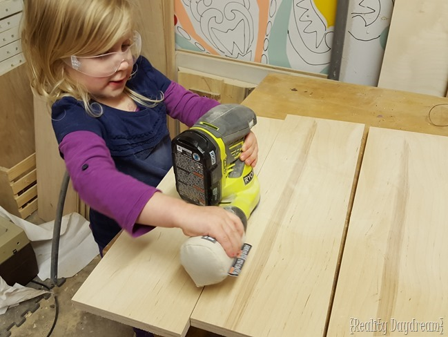 Paisley operating the orbital sander prior to priming the custom DIY rolling kitchen island.