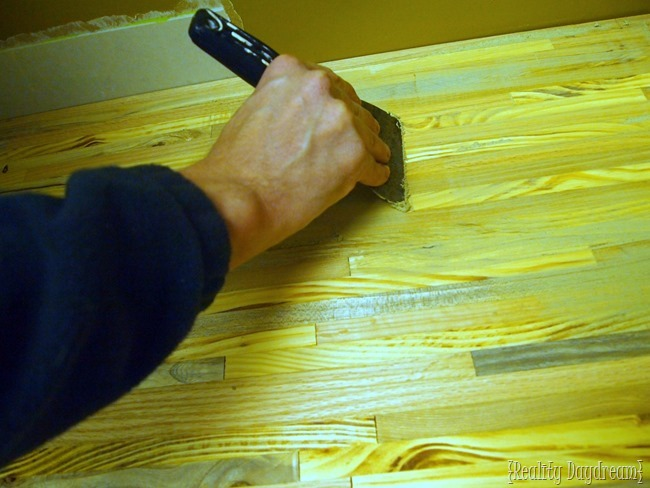 Use a wood filler and a putty knife to apply the wood filler and make sure all the extra holes and spaces in the wood are filled and sealed entirely.