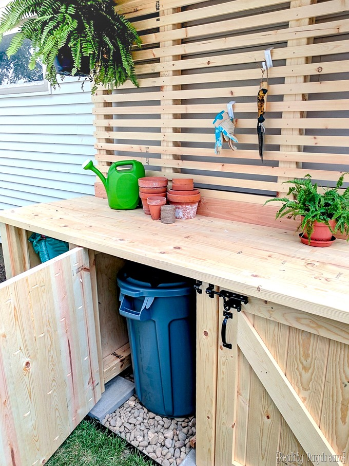 Free building plans for this DIY potting bench with garbage can enclosure {Reality Daydream}