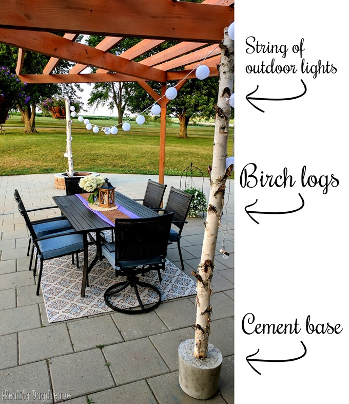 Adding pretty patio lighting using birch logs with cement bases and strings of outdoor lights {Reality Daydream}