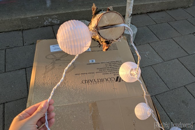 Outdoor lighting DIY... bitch logs set in cement to hold up pretty strand of outdoor lights! {Reality Daydream}