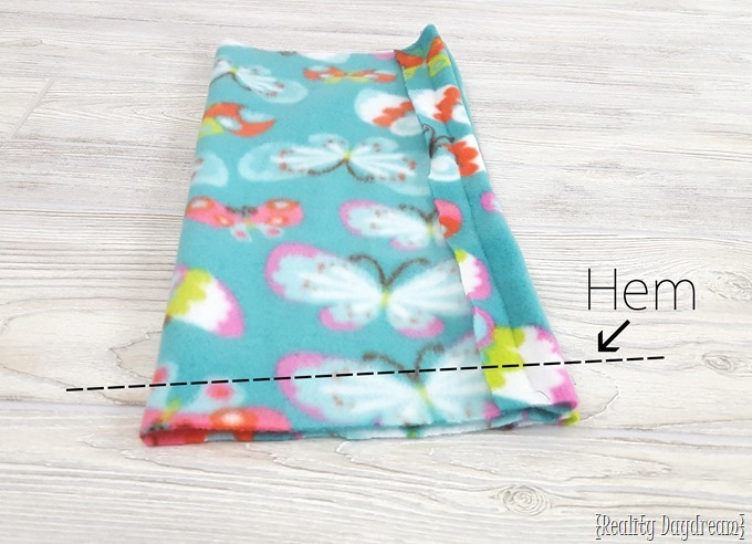 Fold and hemming guide for a hooded fleece-lined car seat poncho.