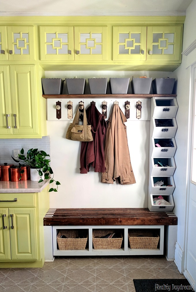 Mudroom integrated into a kitchen entrance, complete with cubbies and baskets for shoes.