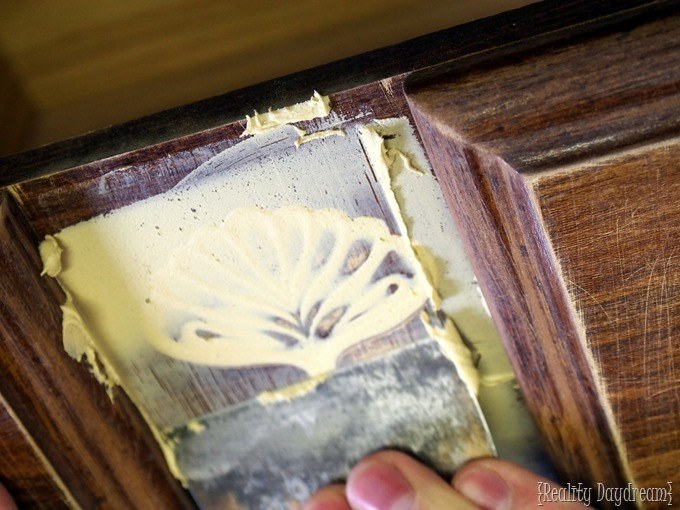 Use a putty knife to crape off excess wood putty when filling decorative carvings in dated furniture {Reality Daydream}