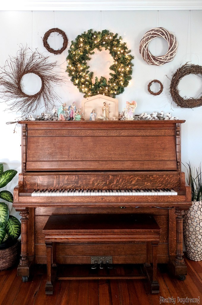 Christmas Gallery Wall and Piano 'Mantel' styled up for the holidays with wreaths and nativity {Reality Daydream}