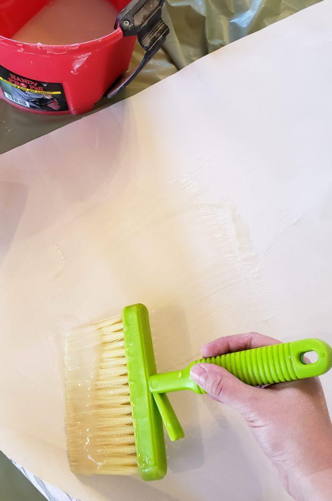 Spread a thin layer of wallpaper paste onto the strip of wallpaper