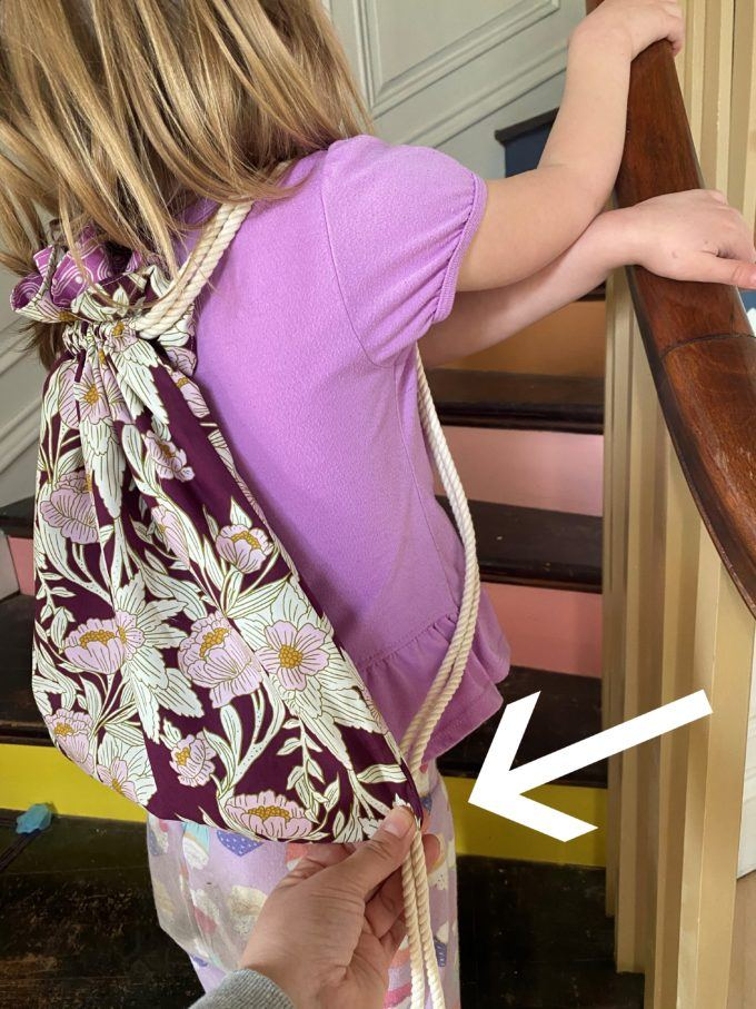 Try the drawstring backpack on the child to see where you want the drawstrings to attach to the bag.